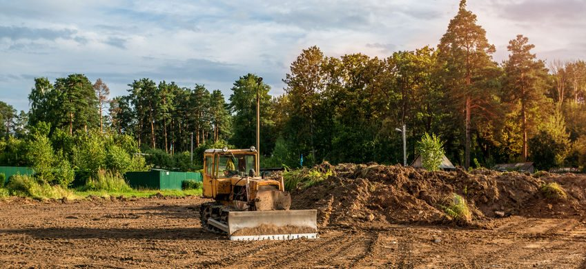 Excavator clearing land for a custom home