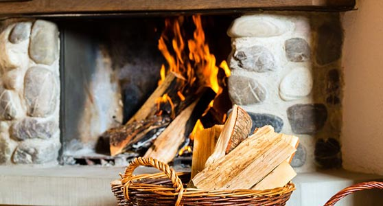 close up photo of fireplace with firewood in a basket