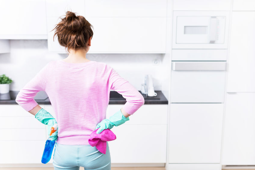 Woman in rubber gloves with hands on hips getting ready to spring clean kitchen