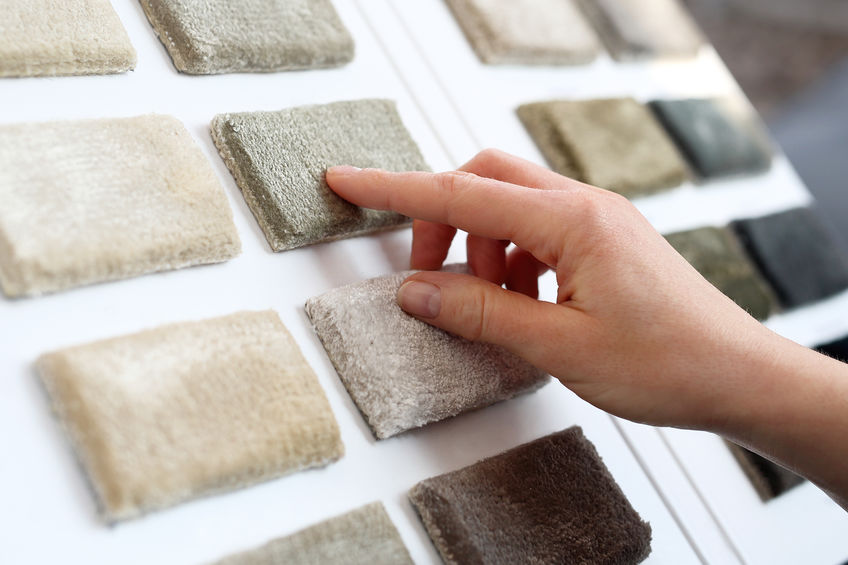 woman looking at and touching carpeting samples