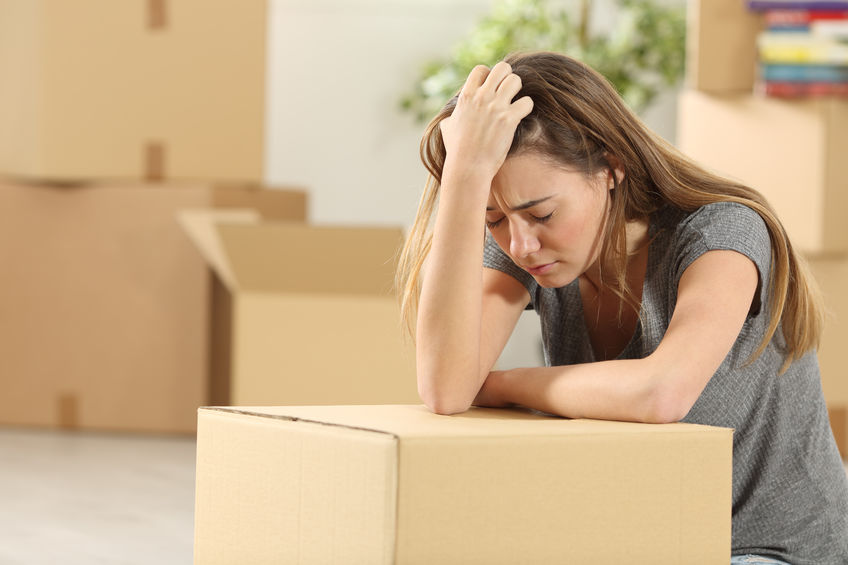 woman with moving boxes regretting her home purchase decision