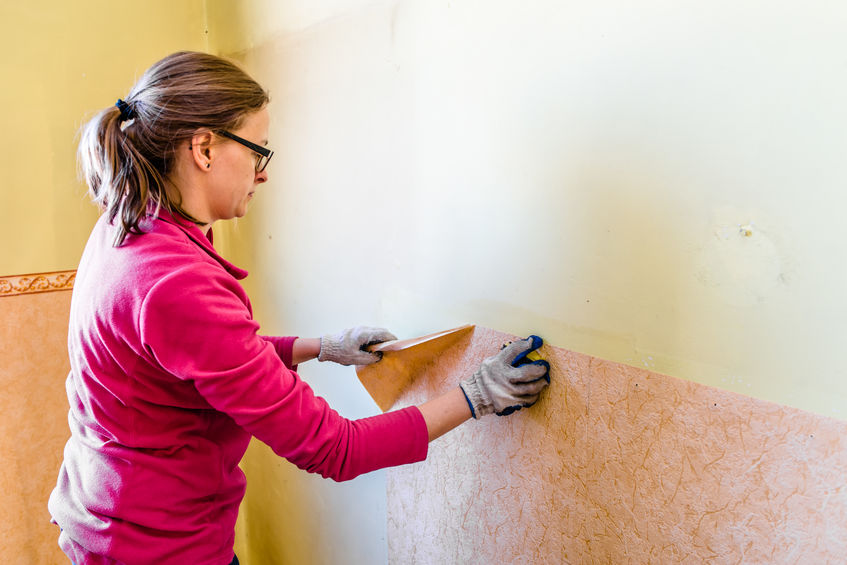 Woman removing old wallpaper from the wall, home renovation