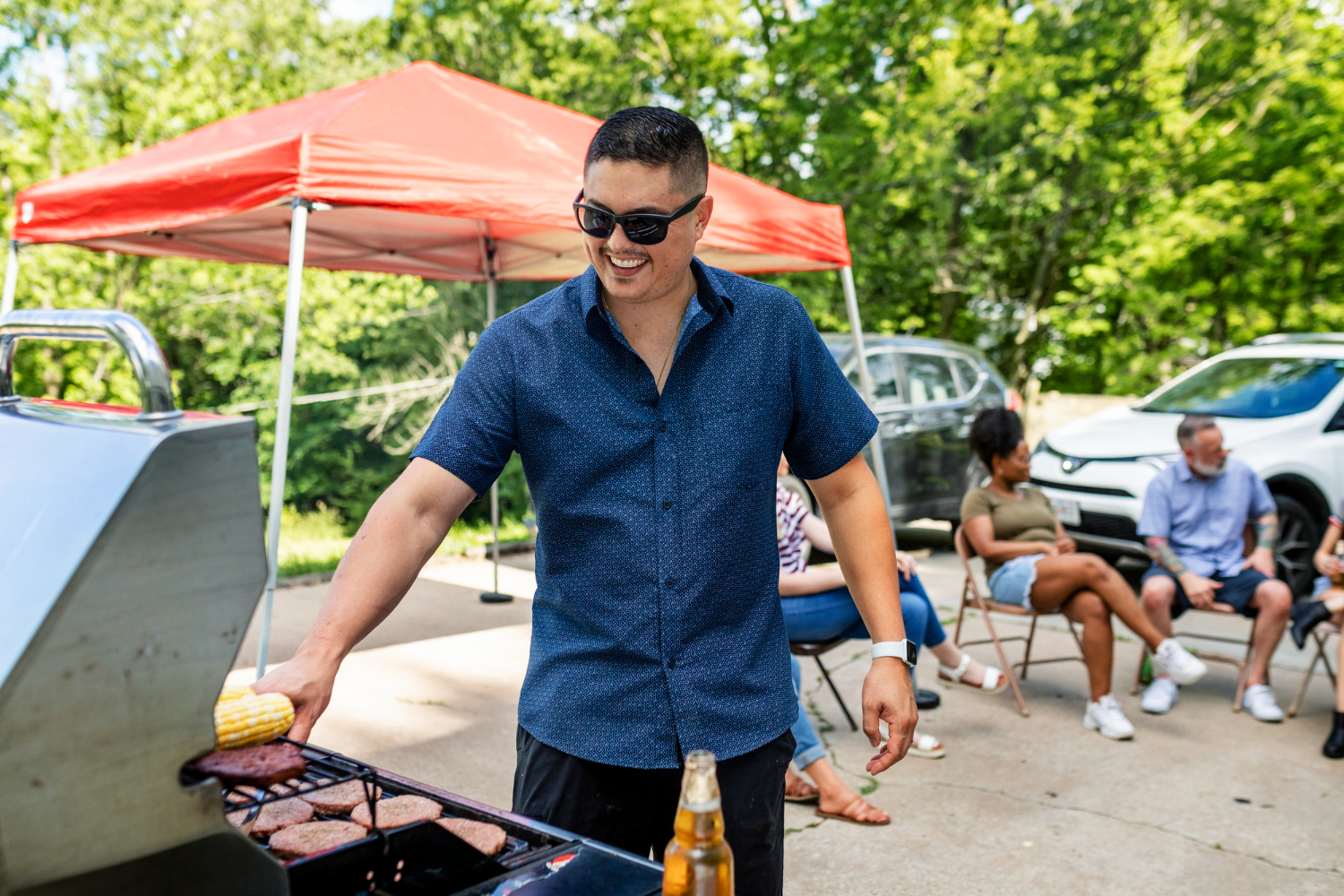 man cooking best tailgating recipes for the big game on the gill in parking lot for friends
