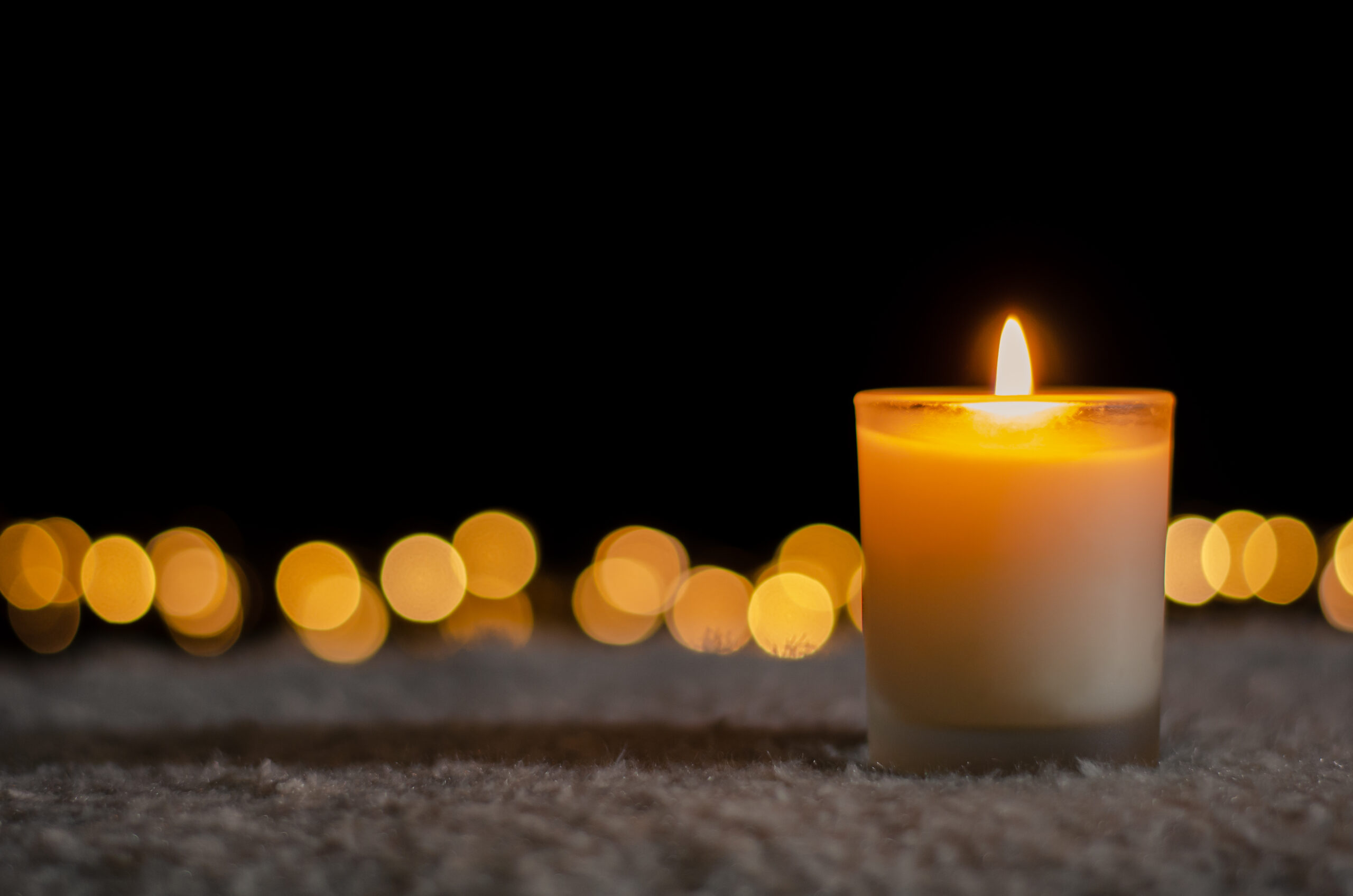 candle lit in home with lights behind