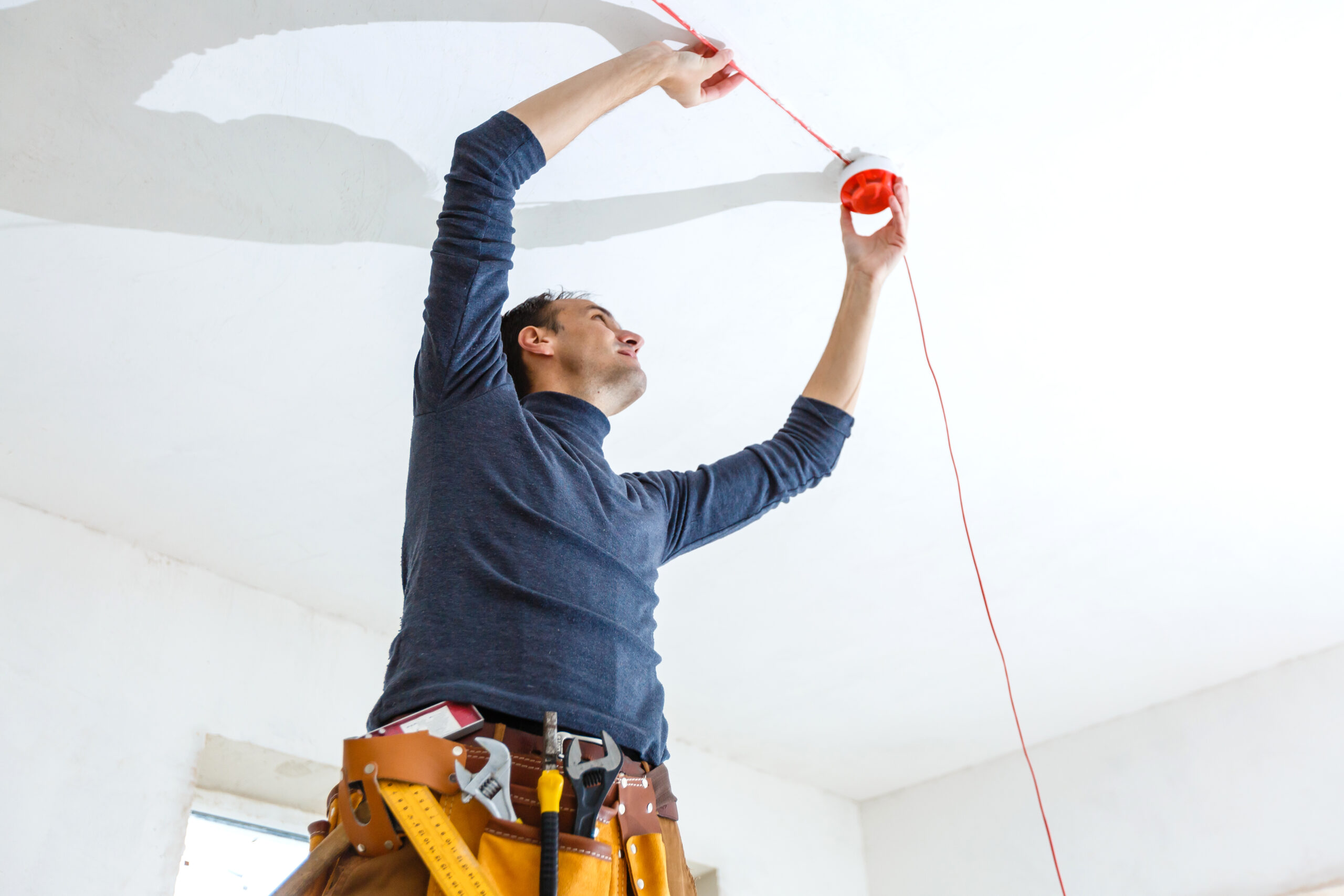 electrician-installing-fire-alarm-system-indoors