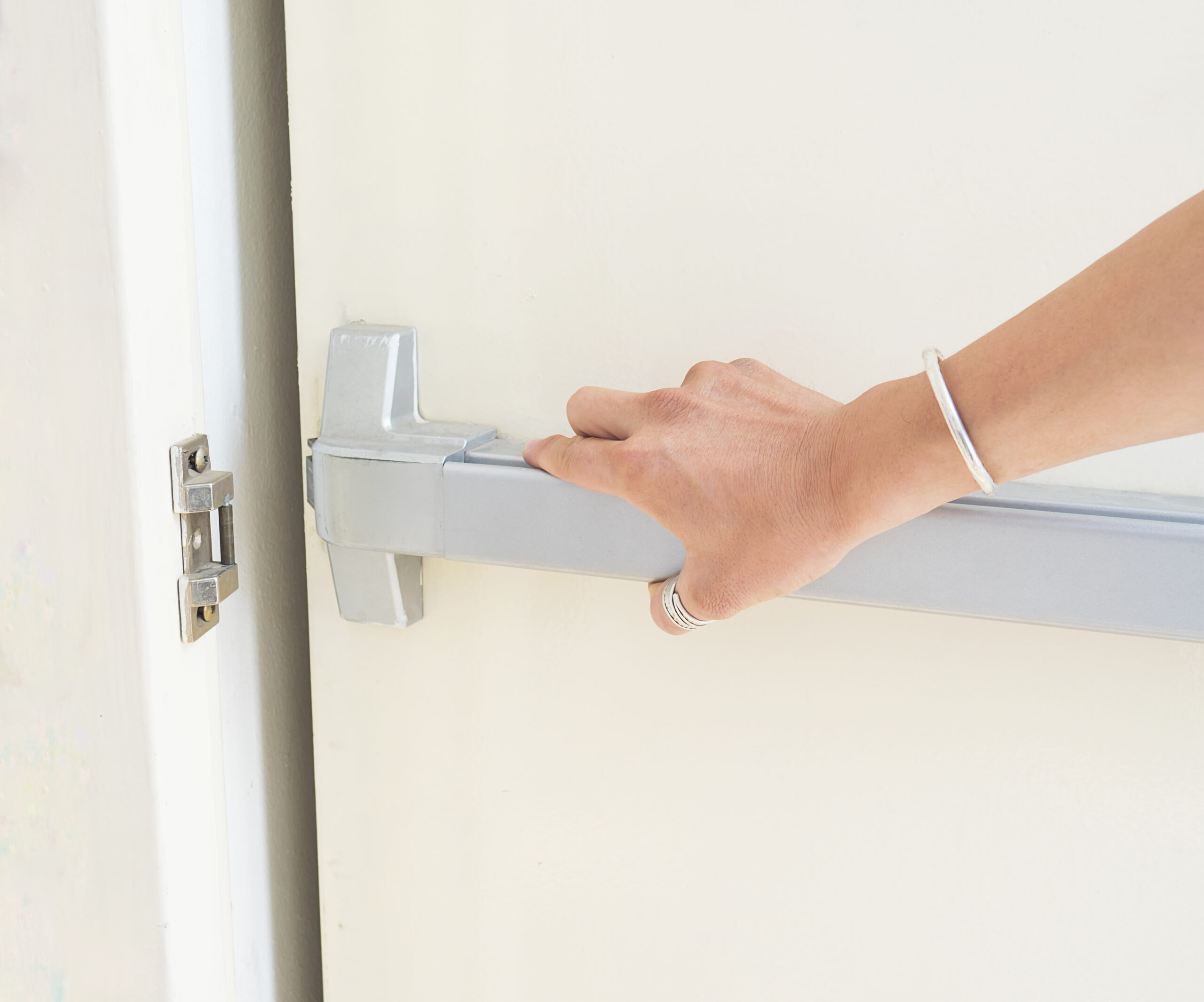 hand-is-pushing-opening-emergency-fire-exit-door-for-escape-plan