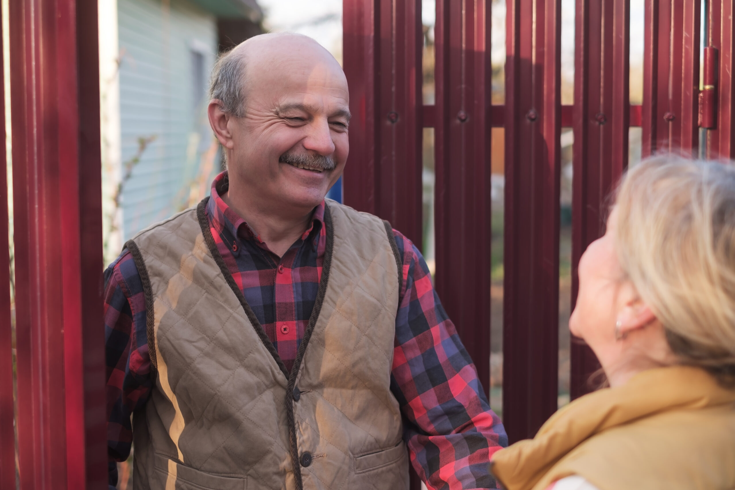 woman having small talk with her neighbor through the fence to be a good neighbor